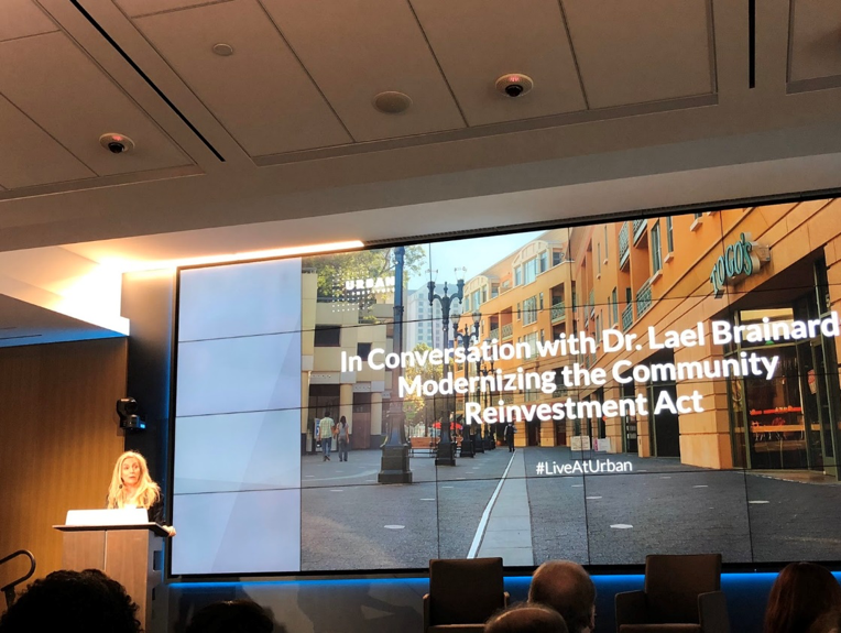 "Lael Brainard gives a presentation to an audience. The screen shows ""In Conversation with Dr. Lael Brainard Modernizing the Community Reinvestment Act"""